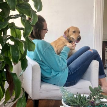 Woman sitting on chair with yellow lab.