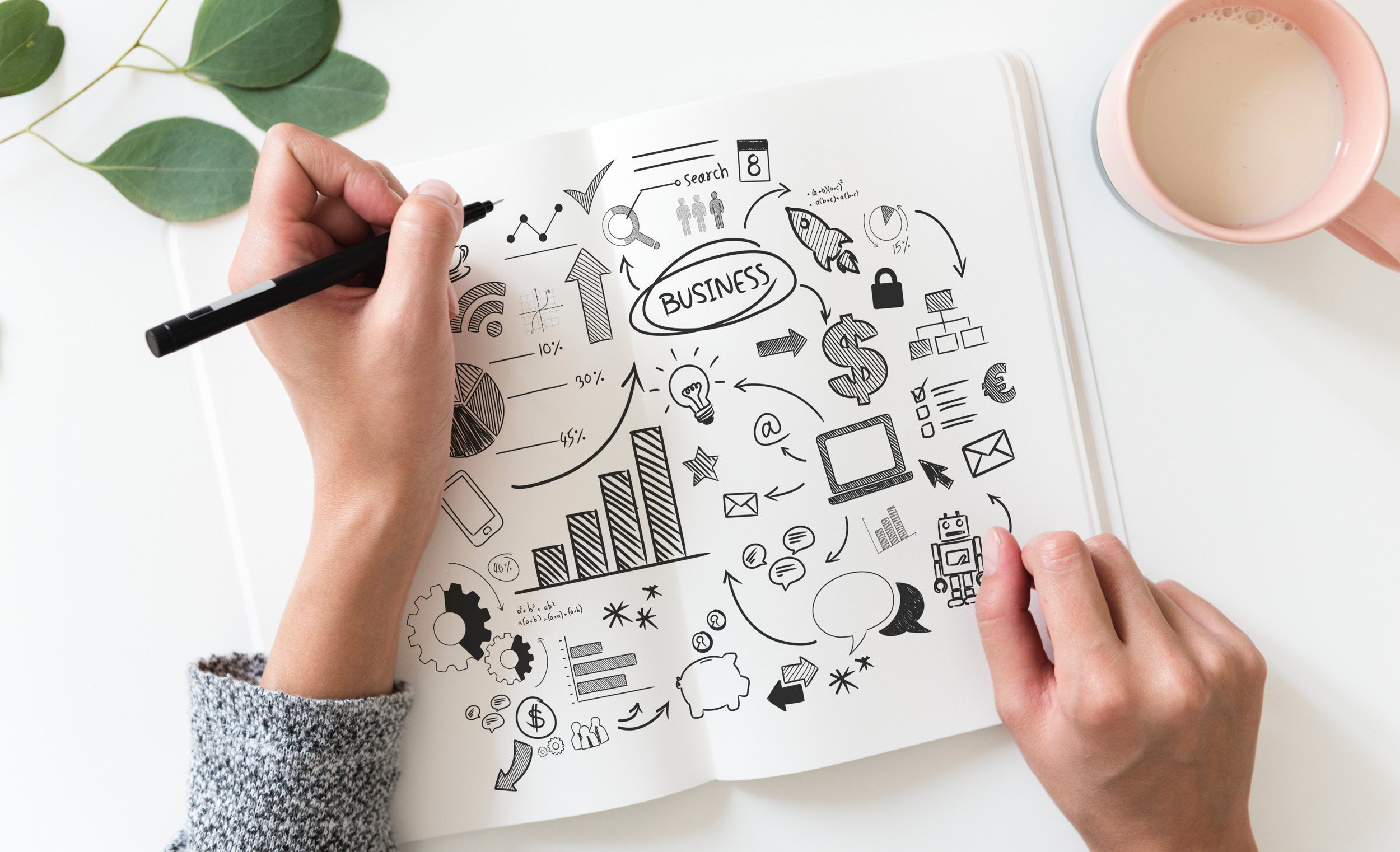 A person sketching icons and other graphics in a notebook with a pen. Visuals such as these can help improve your blogging as well.