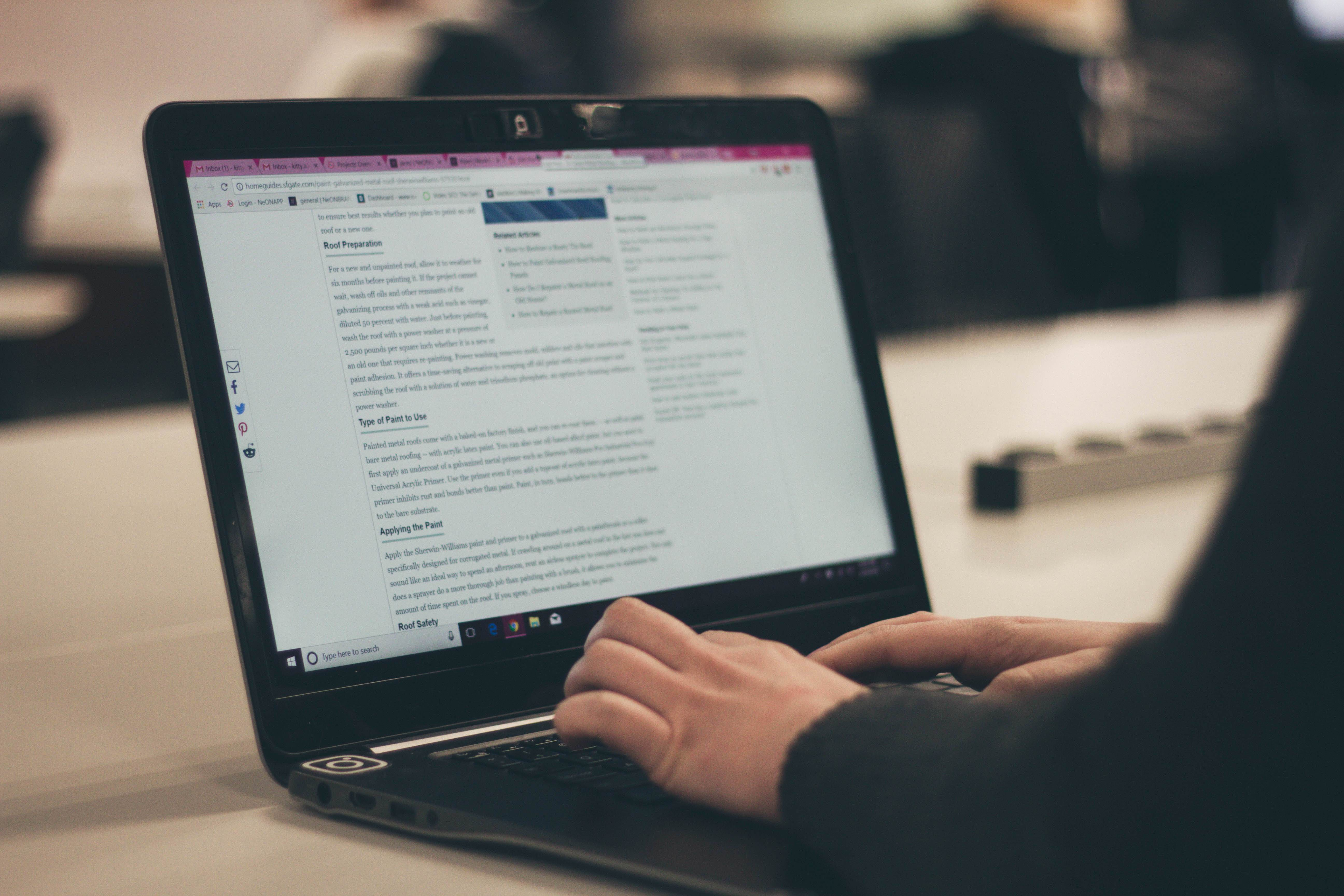 A person typing on a laptop with a blog post organized by different headings on the screen. Making your posts easier to read is another great way to improve your blogging.