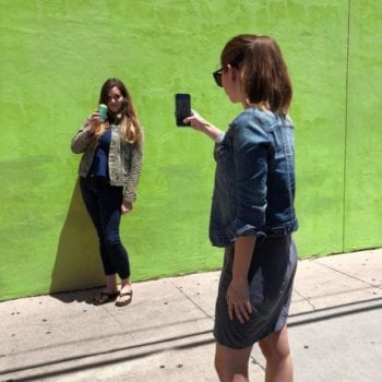 Young woman takes a photo of another woman drinking La Croix by a green wall.