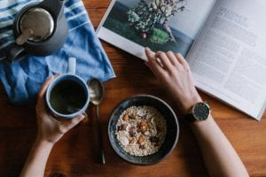 An example of a stock photo from unsplash.com, in which someone holds a cup of coffee while flipping through a book.