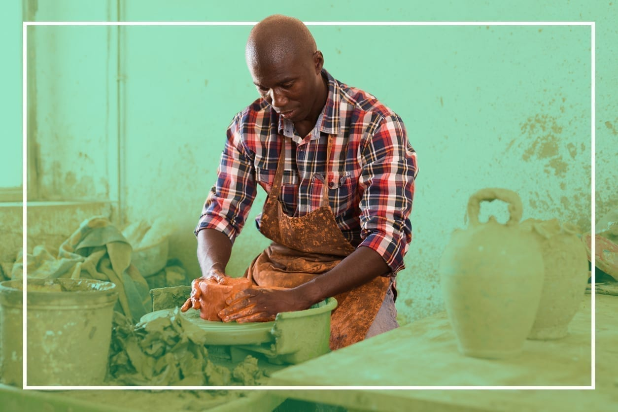 An artist is throwing a bowl on a pottery wheel in a studio.