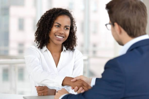 A customer relationship manager shaking hands with a potential client after a meeting. Business development specialist job description