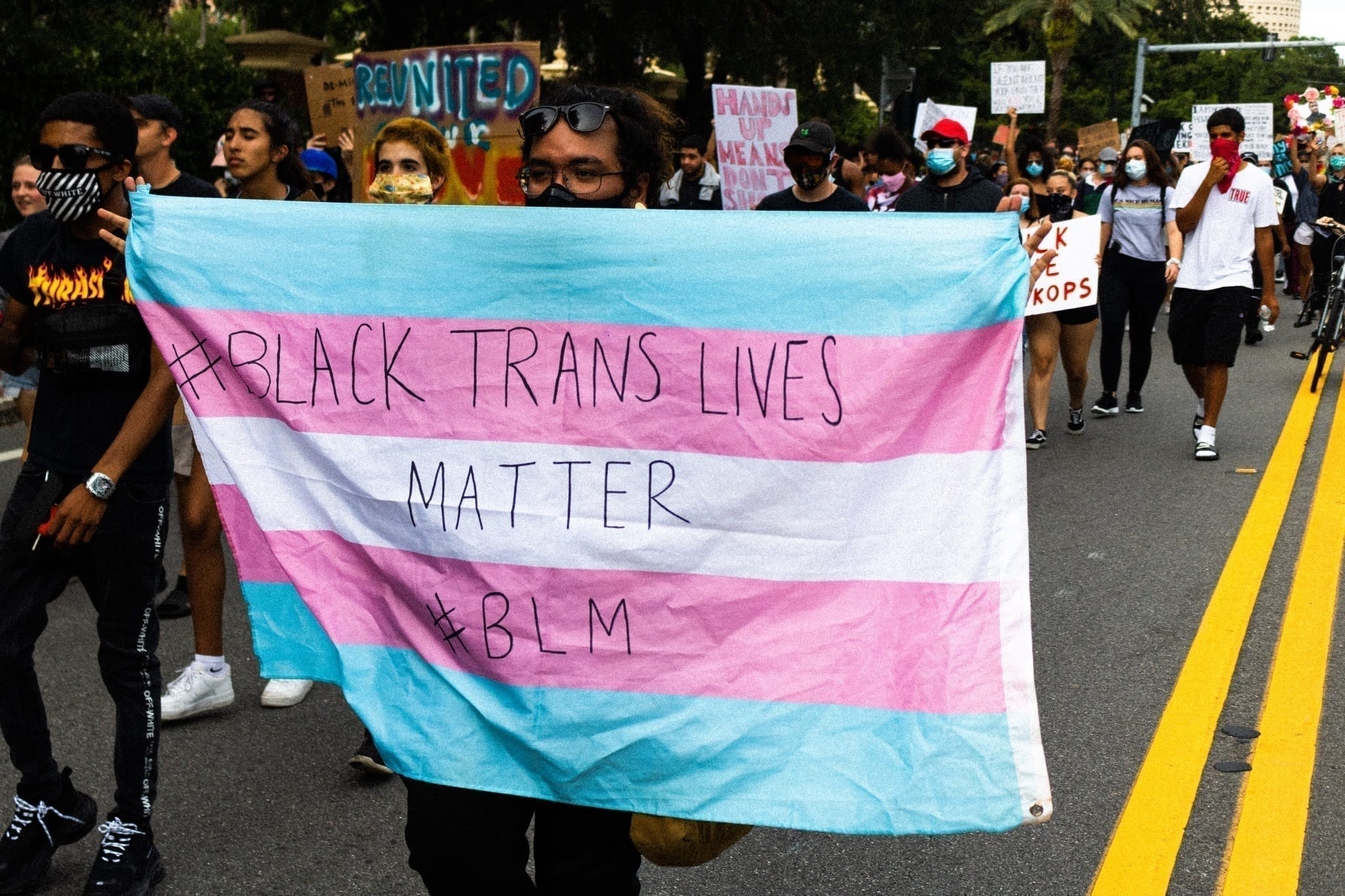"""In a protest, a person holds a blue, pink, and white flag that reads """"Black Trans Lives Matter BLM"""""""